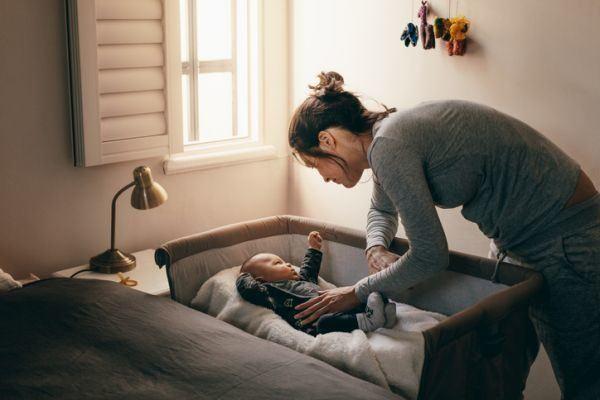 metodo-para-dormir-a-los-ninos-estivill-o-gonzalez-bebe-en-cuna-con-mama-istock