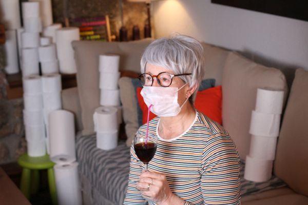 ideas-para-entretener-a-personas-mayores-en-casa-mujer-en-cuarentena-vino-papel-higienico-mascarilla-istock