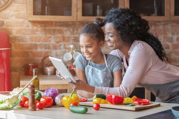 Madre e hija leyendo receta de cocina