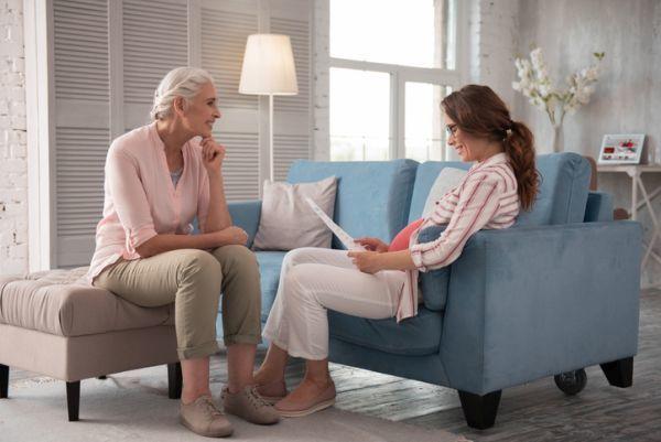 Embarazada leyendo documento con mujer mayor