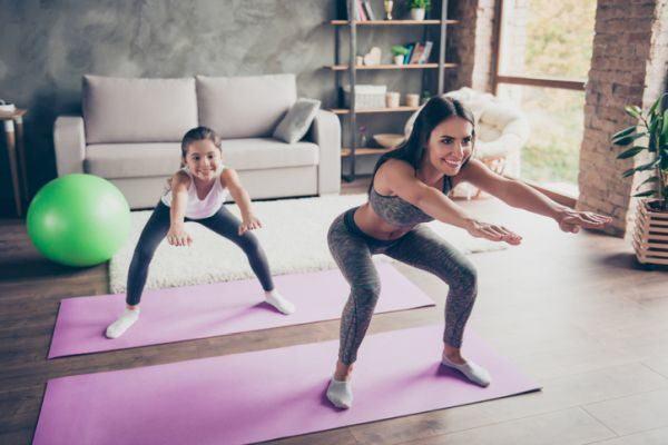 rutina-de-ejercicio-con-ninos-madre-e-hija-salon-sentadillas-istock