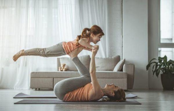 rutina-de-ejercicio-con-ninos-madre-e-hija-salon-vuelo-al-aire-istock